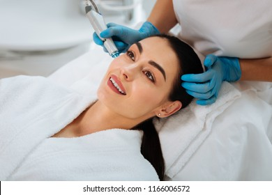 Pleasant beauty procedure. Joyful positive woman smiling while enjoying the beauty procedure