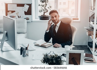 Pleasant business talk. Handsome young man in full suit talking on the phone and looking away while sitting at the office desk