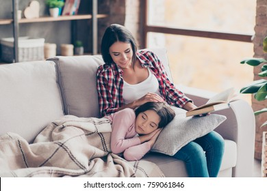 So pleasant and calm daytime sleep! Cute little girl fell asleep on a couch while her careful happy mother was reading a fairy tail