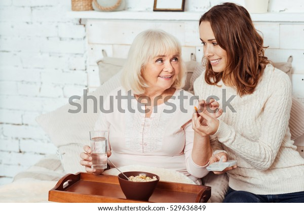 Pleasant caring woman giving pill to her grandmother