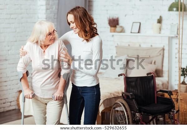Zuvorkommende Betreuerin hilft bei der Rehabilitation ihrer behinderten Großmutter