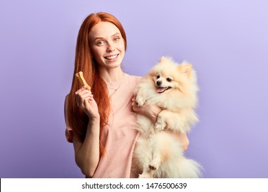 pleasant cheerful girl giving vitamins to her pet. close up portrait, isolated blue background, studio shot.food for domestic animals