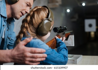 Pleasant cheerful man helping his daughter
