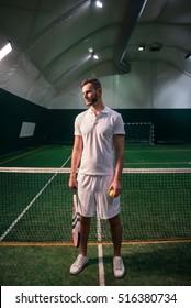 Pleasant confident tennis player standing in the indoor court