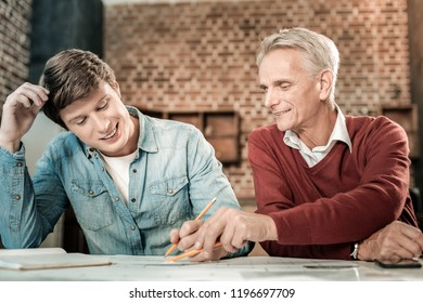 Pleasant cooperation. Nice smart aged man sitting together with his young colleague and talking to him while sharing his experience