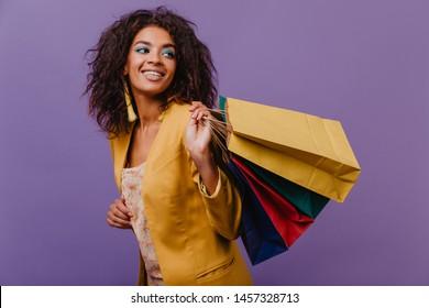 Pleasant curly woman enjoying shopping. Amazing brunette girl posing in yellow jacket.