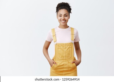 Pleasant cute female dark-skinned employee helping customers find right item to purchase. Joyful friendly-looking girl in trendy yellow overalls, holding hands in pockets and smiling at camera