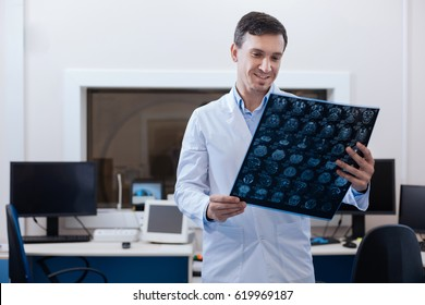 Pleasant delighted radiologist looking at the MRI scan results