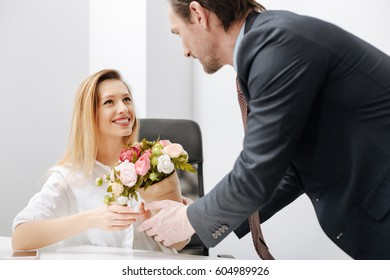Pleasant employer presenting gift to the employee in the office