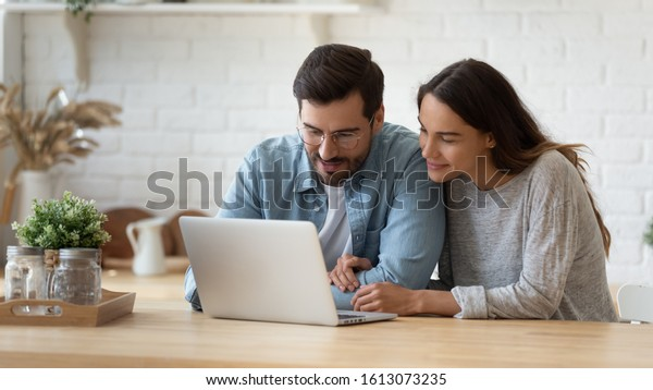Pleasant family couple sitting at big wooden table in modern kitchen, looking at laptop screen. Happy young mixed race married spouse web surfing, making purchases online or booking flight tickets.