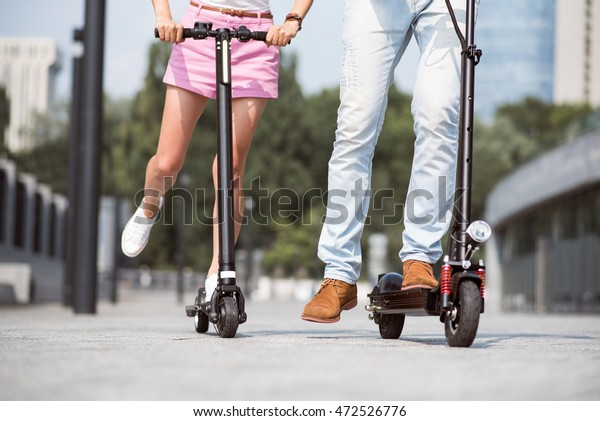Pleasant friends using scooters,