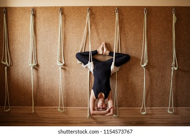 pleasant gifted gymnast is doing bound angle pose upside down on the ropes. a new kind of yoga. full length photo