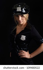Pleasant girl in a uniform of  police officer on a black background