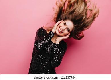 Pleasant inspired girl dancing on pink background. Beautiful brunette woman in black attire having fun.