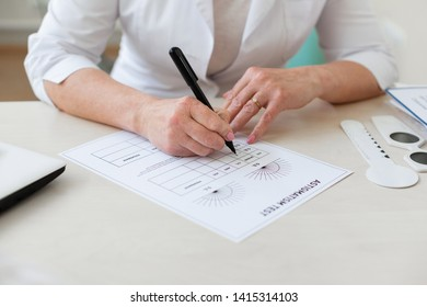 Pleasant kind doctor. Focused ophthalmologist writing down results of astigmatism test on a special lined paper