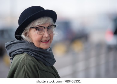 Pleasant lady. Portrait of charming stylish senior female in glasses is standing outside and looking at camera with slight smile. Copy space in the right side