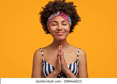 Pleasant looking delighted female with pleased expression, gentle smile and eyes shut, keeps palms pressed, dressed casually, dreams about something pleasant, gestures in yellow studio alone