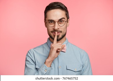 Pleasant looking delightul youg male in round eyewear, keeps finger on lips, asks not tell secret information or keep silence, isolated over pink background. Attractive bearded man gestures at home