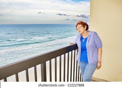 A pleasant looking, red haired, senior woman gazes dreamily off her balcony at the ocean waves feeling the cool ocean breeze on her face.