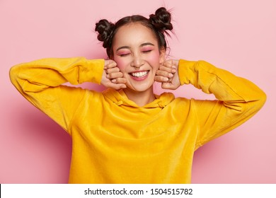 Pleasant looking satisfied Asian lady keeps hands near cheeks, eyes closed, wears yellow velvet hoody, has pink makeup, smiles positively, isolated over pink background. Positive emotions concept