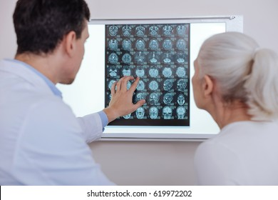Pleasant male doctor showing his patient an X ray photo
