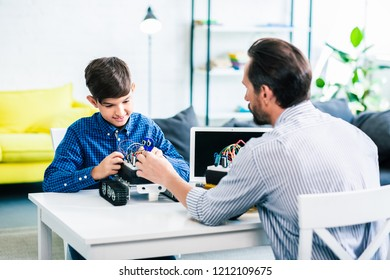 Pleasant man and his smart son constructing robot while sitting at the table