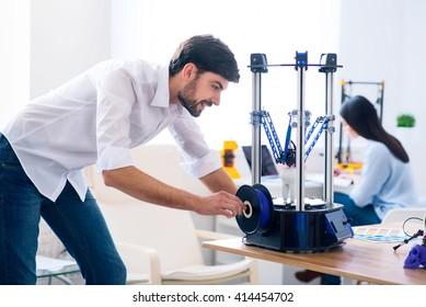 Pleasant man using 3d printer