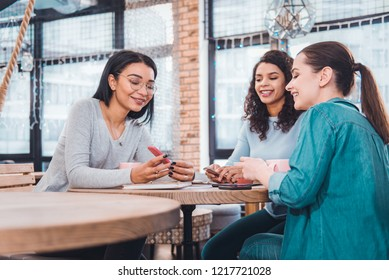 Pleasant meeting. Delighted beautiful woman talking to her friends while showing them her smartphone