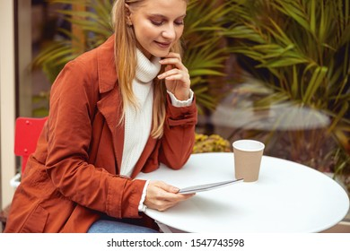 Pleasant millennial girl leaning over her cellphone outdoors