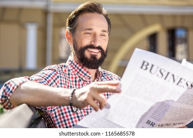 Pleasant morning. Cheerful adult man smiling while reading a daily newspaper