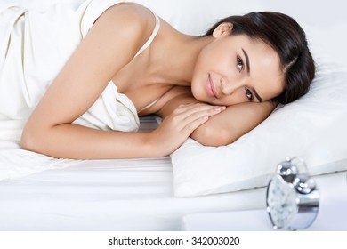 Pleasant morning. Nice beautiful content young woman feeling glad and lying un bed while going to wake up