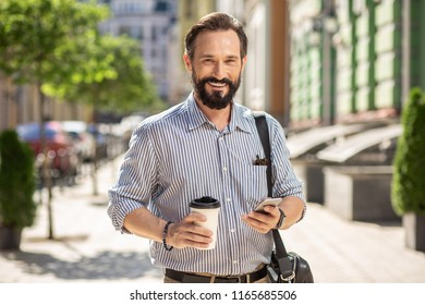 Pleasant morning time. Cheerful handsome man drinking coffee while going along the street