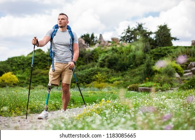 Pleasant motivated man with disability having a Nordic walking training while improving his health