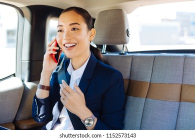 Pleasant news. Happy cheerful businesswoman smiling while receiving pleasant news