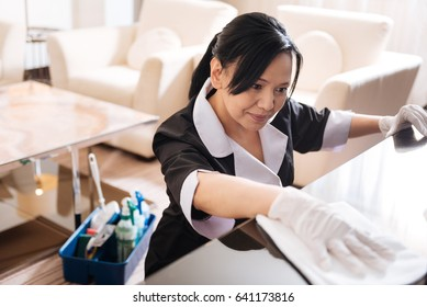 Pleasant nice hotel maid cleaning the hotel room