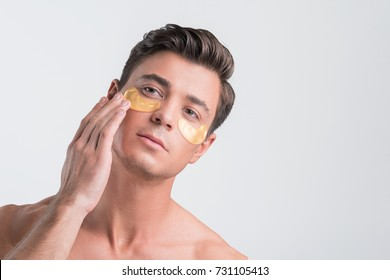 Pleasant nude guy is using anti-wrinkle mask