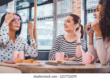 Pleasant pastime. Nice smart woman putting a note on her forehead while playing a guessing game with her friend