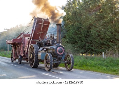 Pleasant Point, Canterbury, New Zealand - October 22 2018: A traction engine steams down a rural road towing antique farm equipment