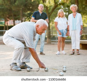 Pleasant positive smiling family playing petanque in outdoor