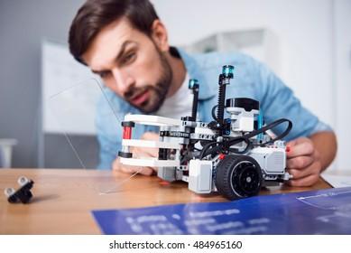 Pleasant professional man testing robot