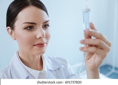 Pleasant professional nurse looking at the IV drip bottle