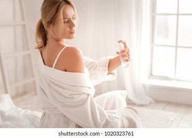 Pleasant refreshment. Attractive nice pleasant woman sitting on the bed and using body spay while caring about her beauty