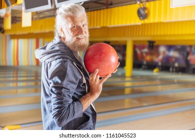 Pleasant relaxation. Nice bearded man smiling to you while holding a bowling ball in his hand