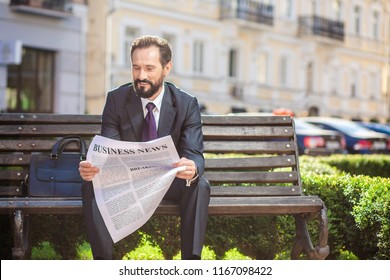 Pleasant rest. Cheerful pleasant businessman reading a newspaper while resting on the bench