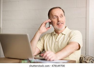 Pleasant senior man talking on cell phone