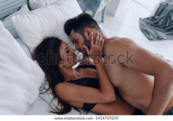 感じが良い。ベッドに寝ながら恋をする美しい若い夫婦のトップビュー