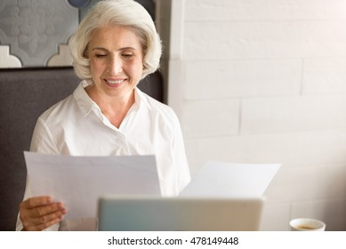 Pleasant serious senior woman working with papers