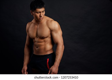 pleasant serious shirtless athlete with perfect abs. copy space. studio shot
