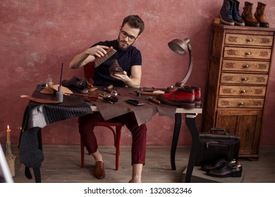 pleasant shoeshine man polishing elegant footwear indoors. full length photo