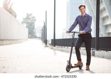 Pleasant smiling man riding a kick scooter